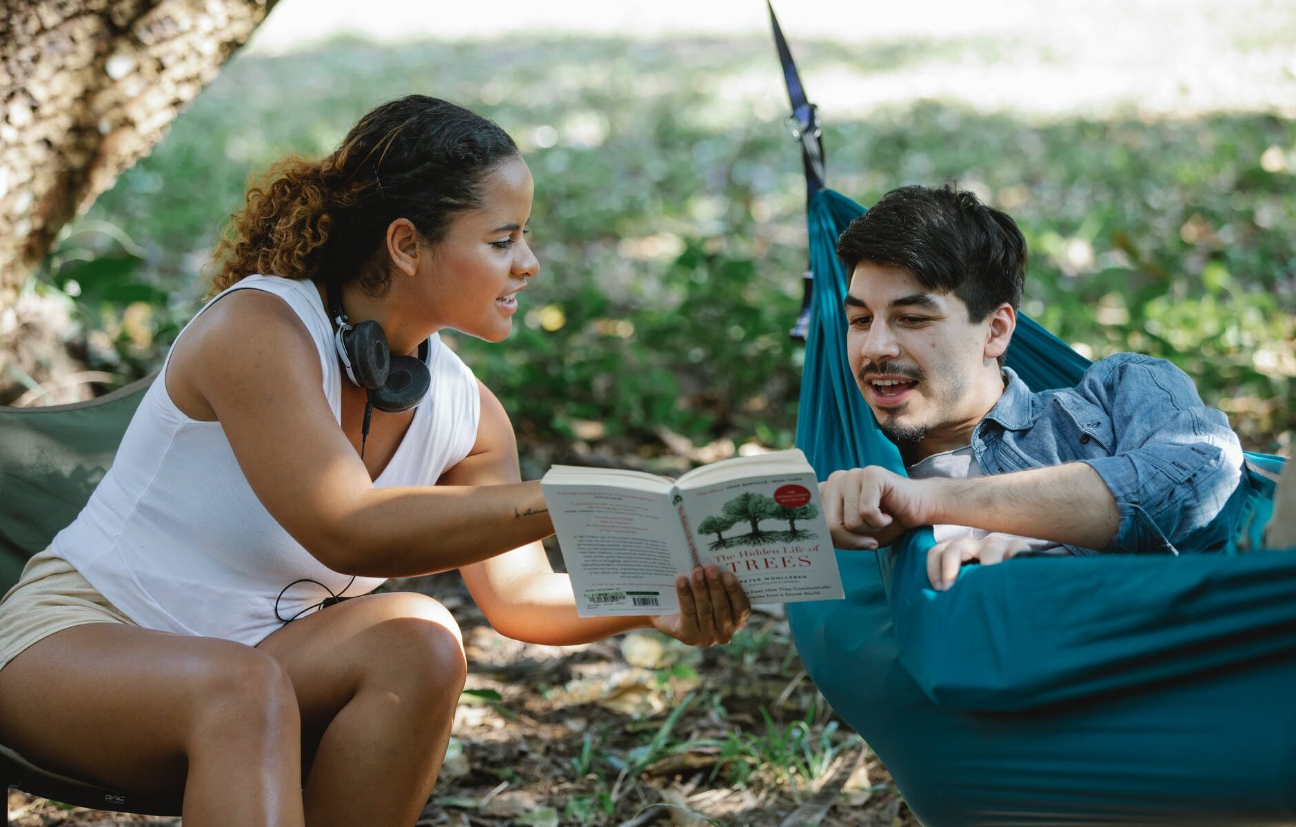 positive diverse couple with book in forest